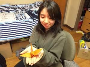Taniguchi with a paper crane she folded