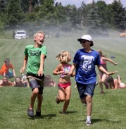 Jeffrey Zeilinger (left), 12, Kaylan Zeilinger, 7, and Larry Krejci, 11, run through water sprayed from a hose during a Youth Playgrounds event on July 9, 2018, at Colby Lake Park in Woodbury. Hannah Black / RiverTown Multimedia