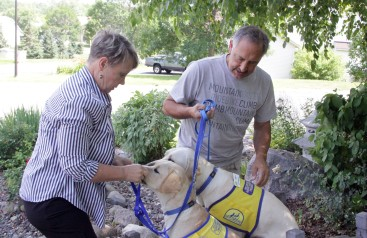 Jeanne (left) and John Segar give their two service-dogs-in-training treats on July 30, 2018, in Woodbury. Hannah Black / RiverTown Multimedia