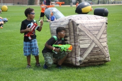 Two toy battle participants prepare to confront opponents behind a blow-up obstacle on Aug. 11, 2018, at East Ridge High School in Woodbury. Hannah Black / RiverTown Multimedia