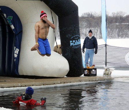 A man braces for being submerged in the icy water as he jumps into Carver Lake. Hannah Black / RiverTown Multimedia