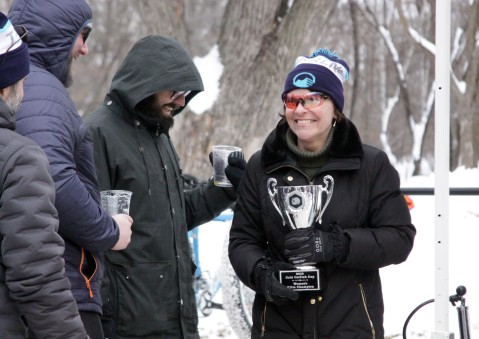 Martha Flynn of St. Paul grins after filling her trophy with beer from a keg. Flynn won the Women's Elite race Feb. 17 at the 2019 Cold Catfish Cup in Woodbury. Hannah Black / RiverTown Multimedia