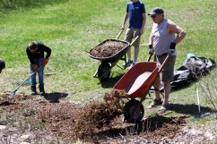 Dave Best dumps fresh mulch from a wheelbarrow during a rain garden clean-up May 4, 2019, in Woodbury. Hannah Black / RiverTown Multimedia